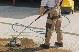 A Man Using a High Grade Pressure Washer To Wash His Driveway